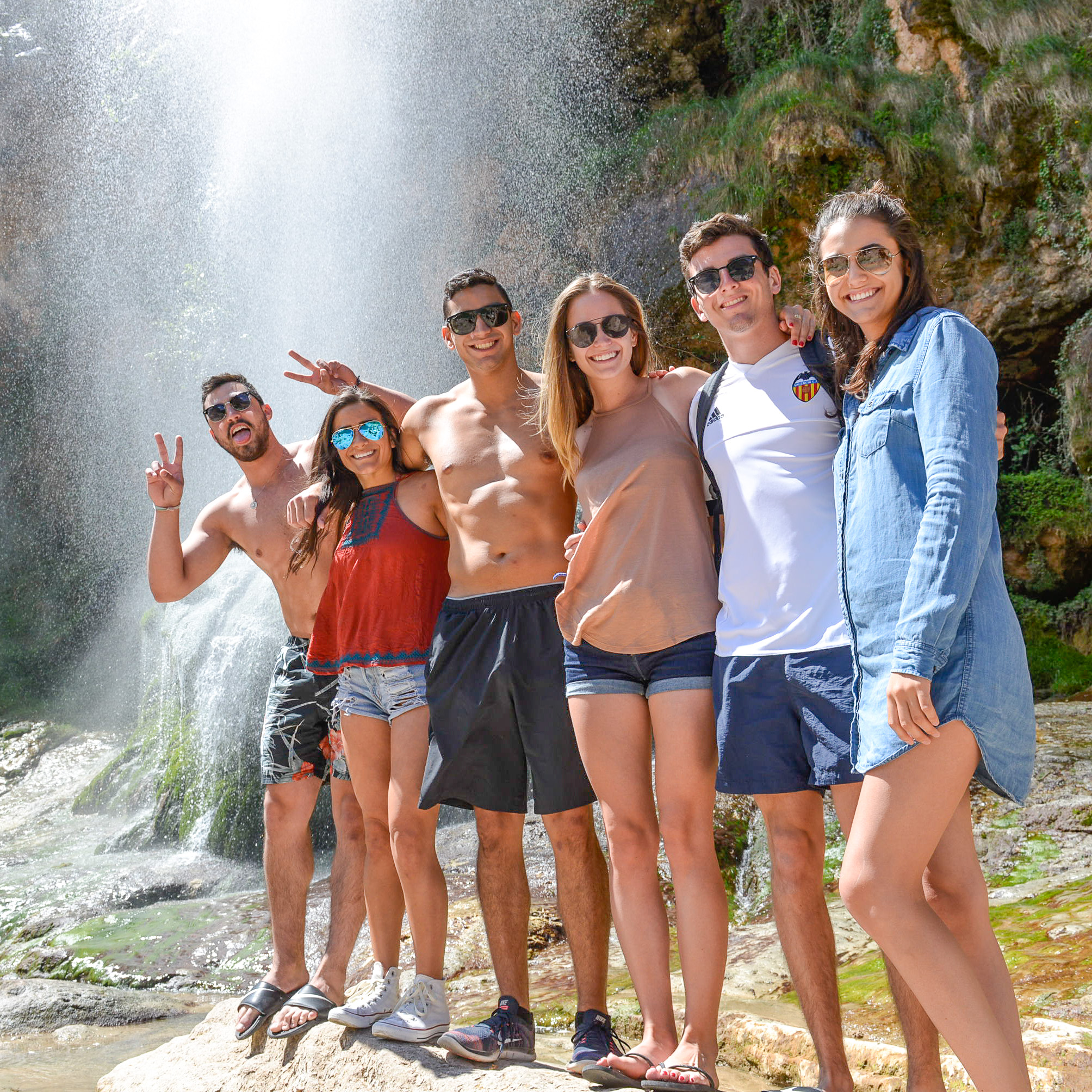 A group of friends enjoying the waterfall, part of the hot springs tour